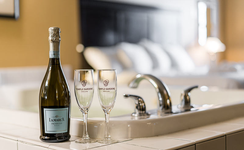 Bottle of Proseco with 2 champagne flutes by bathtub in room