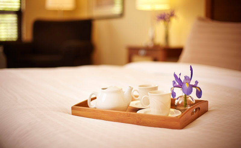 Guestroom with tea tray on bed at Temple Gardens Hotel & Spa